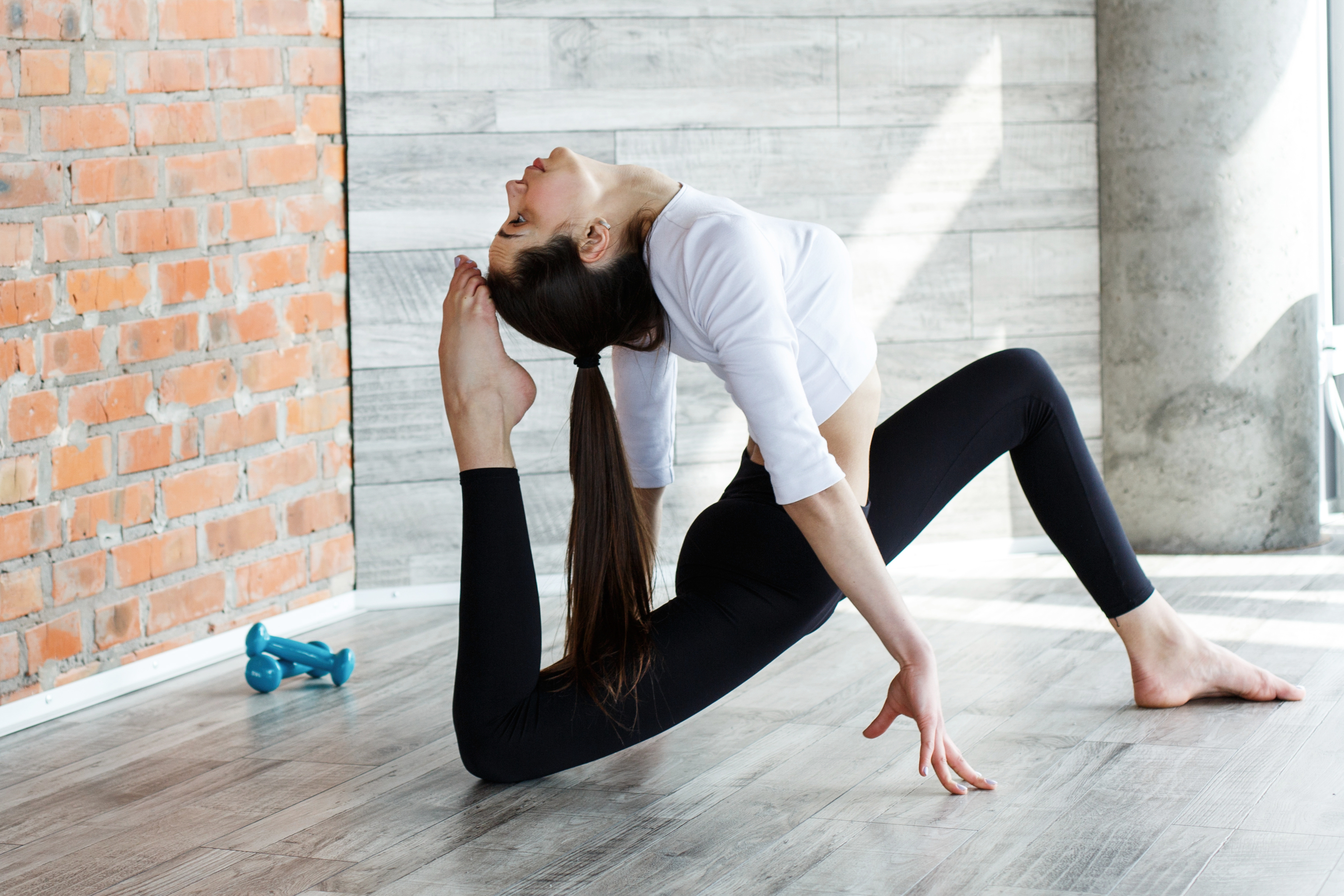 Brunette girl in black and white sport clothes does yoga and str