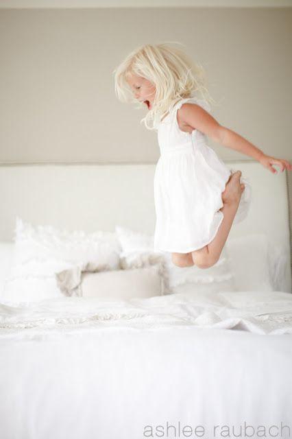 Petite fille sautant sur un lit