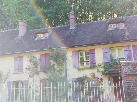 Maison de campagne fleurie aux volets colorés